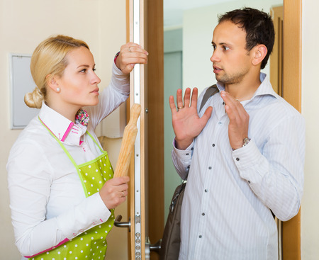 rollingpin: Angry serious woman threatens with rolling-pin for a frightened man