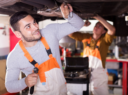 car mechanic: Portrait of two cheerful car mechanics at workshop at work Stock Photo
