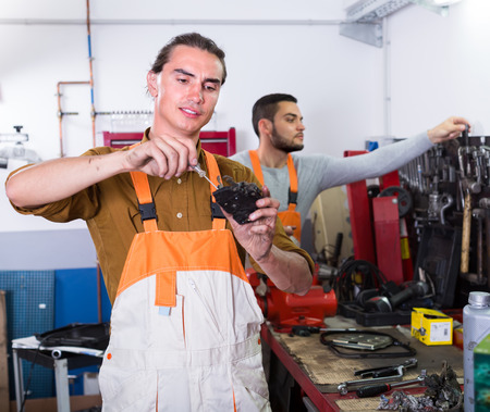 toiling: Portrait of two professional workers in uniform at workshop. Selective focus Stock Photo