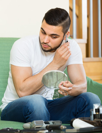masculinity: Young handsome guy using trimmer for removing hair in his ear Stock Photo