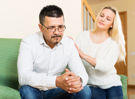 fracas: Loving woman tries reconcile with sad man after quarrel. Focus on guy