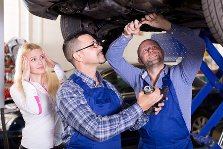 specialists: Portrait worried young girl and specialists at auto repair shop. Focus on the right man