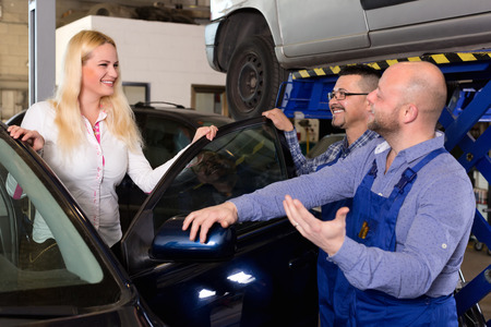 car mechanic: Two troubleshooters showing fixed car to cheerful client