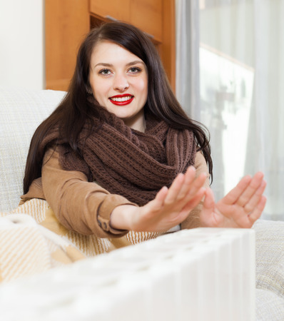 woman  in scarf  warming near warm heater  in home