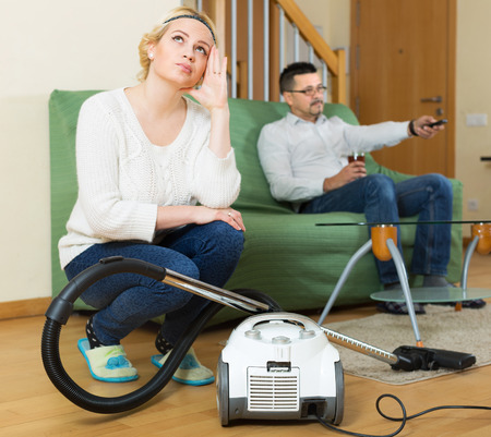 hoover: Tired woman with hoover looking at man on sofa watching TV Stock Photo