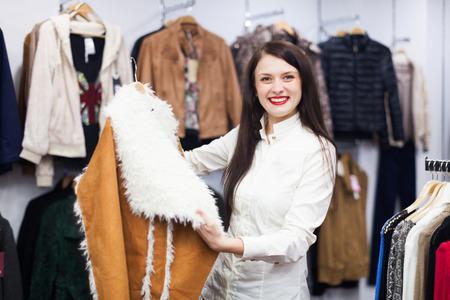 ordinary woman: Ordinary woman looking at jacket at clothing store