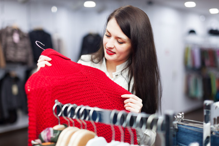 'pull over': Smiling female buyer choosing sweater at clothing store