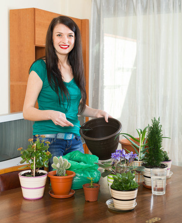 replant: Happy woman transplanting flowers plant in flowerpot at  home Stock Photo