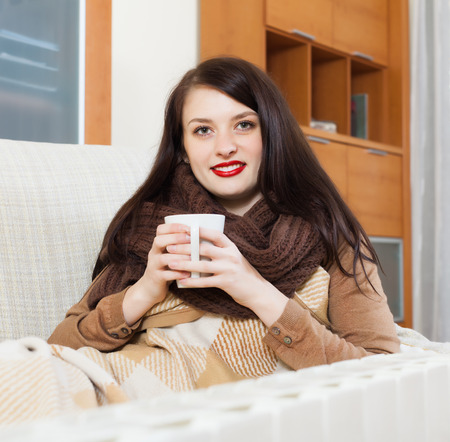girl with cup near electric heater in home Stock Photo
