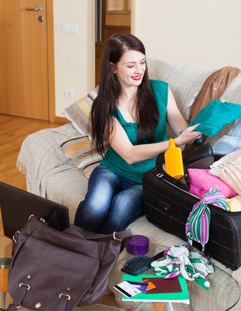 young add: Happy brunette woman packing suitcases at home going on holiday Stock Photo