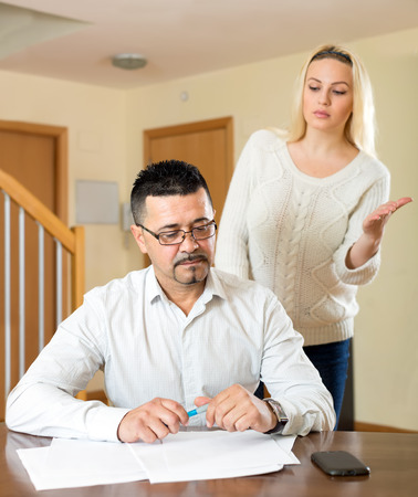 nagging: Spouses having a domestic quarell over financial problems they are having. Husband is sitting at the table looking at important papers while his wife is nagging him