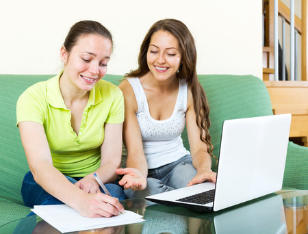 Girl looking papers with laptop at  home. Focus on the left woman photo