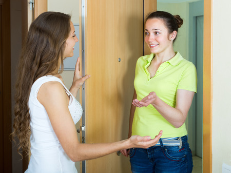kindred: Cheerful young woman meeting girlfriend at the door Stock Photo