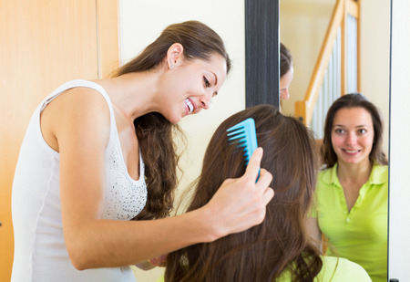 cognate: Cheerful smiling girl brushing her friend in front of the mirror at home Stock Photo