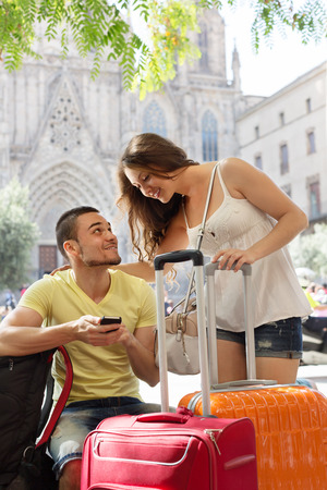 navigating: Happy young travellers using smartphone navigating system in city