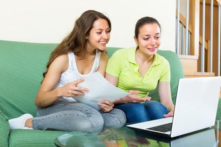 parsimony: Smiling women looking financial documents with laptop in home interior