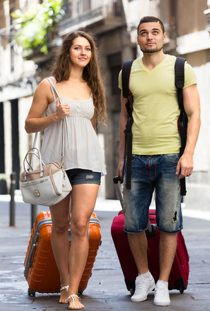 Smiling man and woman in casual clothes with luggage on city background photo