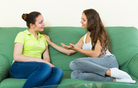 blabber: Two cheerful smiling young women gossiping on sofa at home
