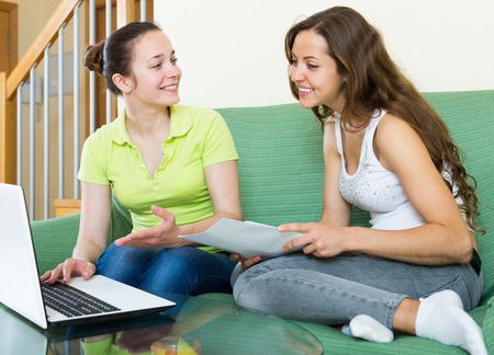 Smiling women looking financial documents with laptop  in home interior Stock Photo