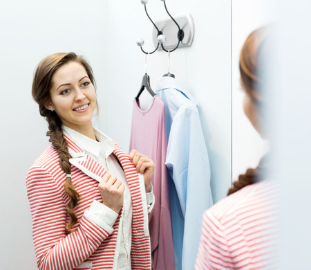 brune: smiling young female with new garment at fitting-room
