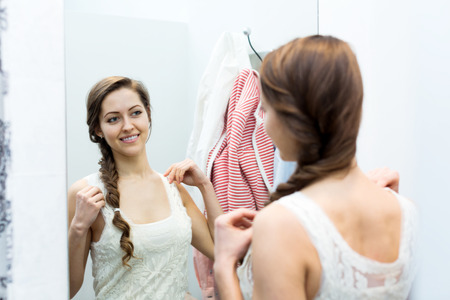 brune: Portrait of happy young female with new garment at fitting-room Stock Photo