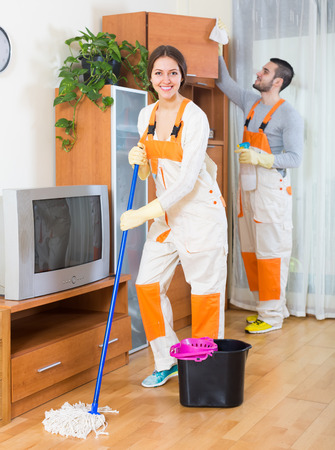 cleaning business: Professional cleaners team in uniform working at clients home with equipment. Focus on girl