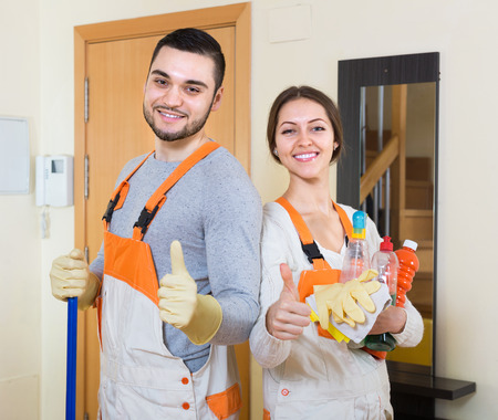 houseman: Portrait of smiling professional cleaners with equipment at door of client house
