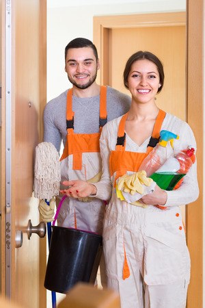 company premises: Portrait of professional cleaners with equipment standing at doors of client house