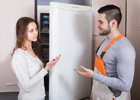 aftersales: Female client and warranty service man near fridge at kitchen. Focus on woman