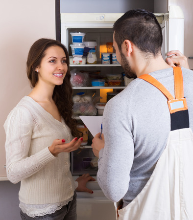 aftersales: Positive female client and warranty service man near fridge at kitchen