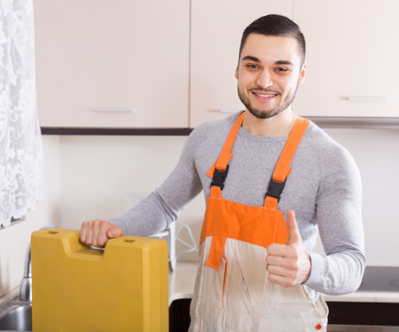 aftersales: Professional plumber successfully working at home of client Stock Photo
