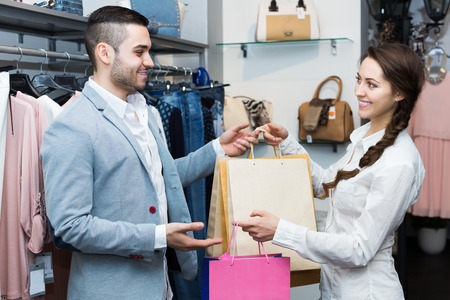 store clerk: Store clerk serving purchaser at fashionable apparel store