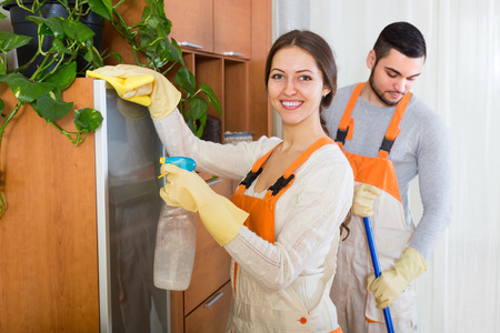 houseman: Portrait of smiling professional cleaners team with equipment at the work in client house