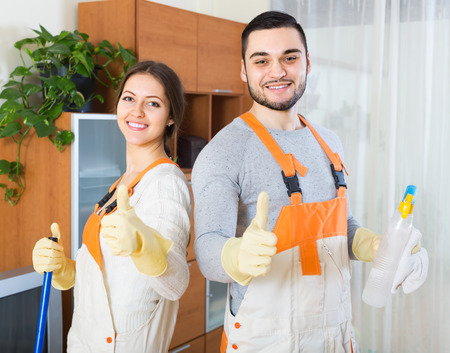 houseman: Portrait of smiling professional cleaners team with equipment at client house Stock Photo