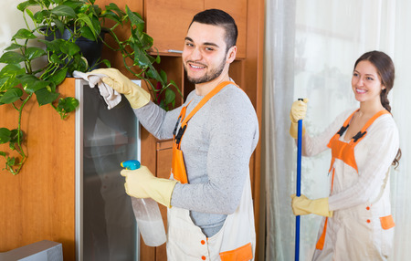 company premises: Portrait of smiling professional cleaners team with equipment at the work