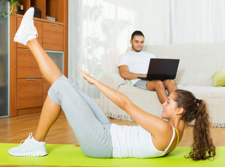 exercices: Guy browsing web while girl doing exercices indoor Stock Photo