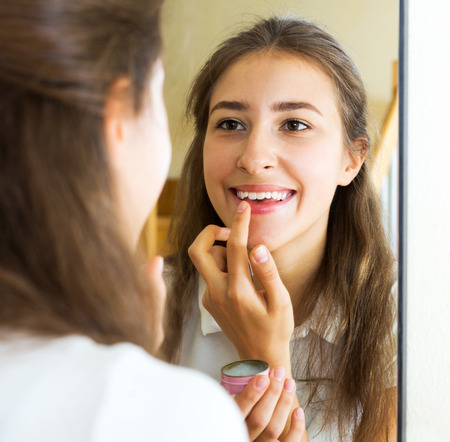 finger on lips: Portrait smiling girl looks in the mirror and uses lip balm Stock Photo