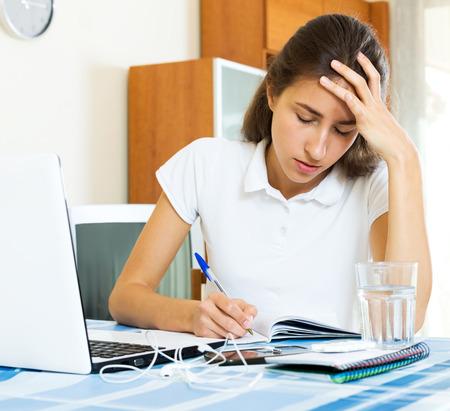 solter�a: estudio estudiante universitaria cansado sentado en una mesa en su casa Foto de archivo