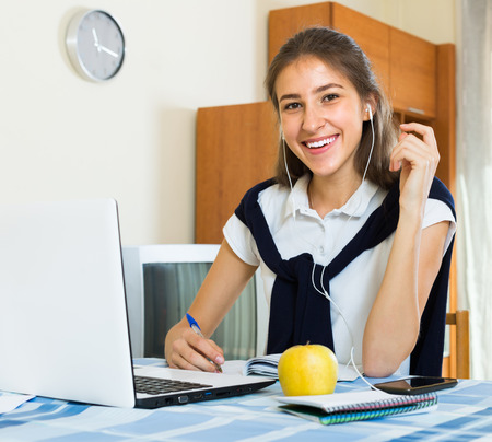 armenian woman: Smiling young girl using laptop and writing at home