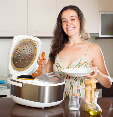Girl cooking with new household multicooker at home photo