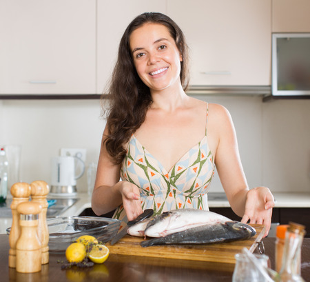 gilthead bream: Smiling young brunette woman with fish at home kitchen