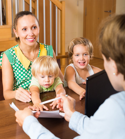 delinquency: Smiling woman and two daughters sitting in front of social worker Stock Photo