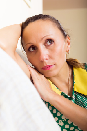 aloneness: sad  middle-aged woman sitting on sofa at  home