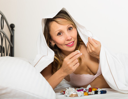 furtively: Smiling blonde woman secretly eating candy in bed Stock Photo