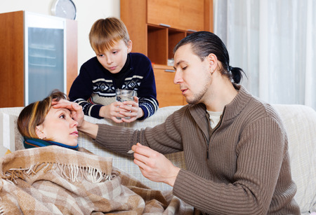 nosotrophy: Man and son caring for unwell woman who has high temperature Stock Photo
