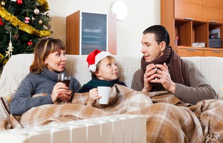 Happy family with teen warming at Christmas time or winter holiday season at home photo
