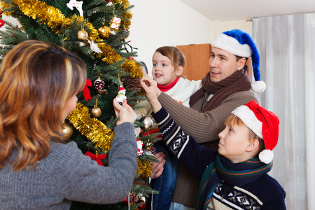 family decorating Christmas tree in living room at home photo