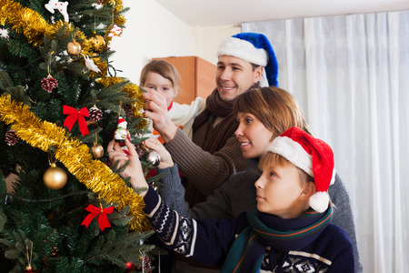 home decorating: Happy parents with children decorating Christmas tree at home