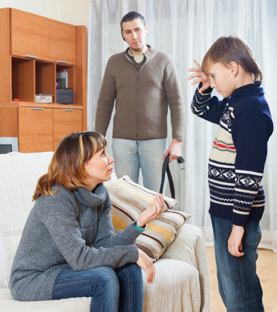 fracas: Mother and father with belt  scolding teenager son at living room Stock Photo