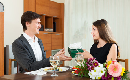 receives: Man receives a gift from the girls at dinner